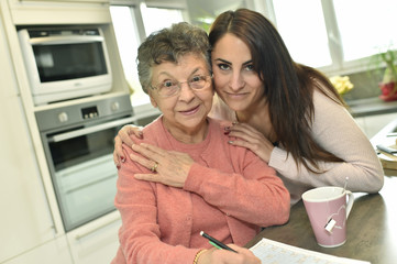 Portrait of elderly woman with granddaughter at home
