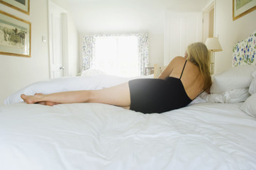 A blonde haired woman lying on her side on a bed.