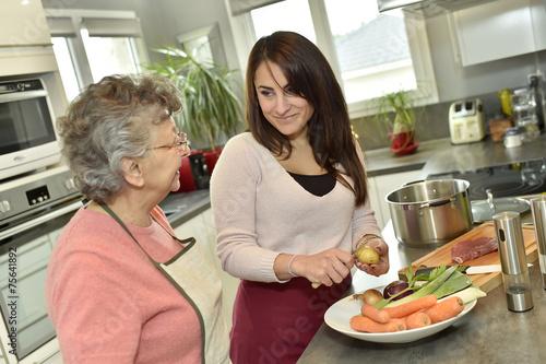 Homecare cooking dinner for elderly woman - 75641892