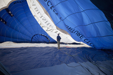 Man standing inside a partially inflated hot air balloon.