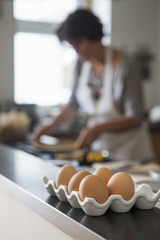 A woman cooking at a kitchen table. A tray of hen's eggs.