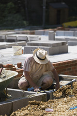 A man working on a construction site, laying foundations for a building.