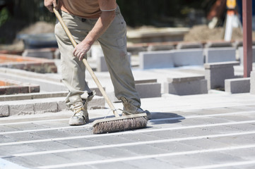 A man using a brush on a cement floor on a construction site.