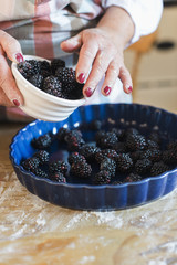 A woman pouring fresh blackberries into a dish.