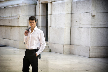 Elegant young businessman outdoor, marble wall and ground