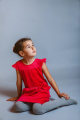 calm girl teenager sits in a red dress looking to the side on