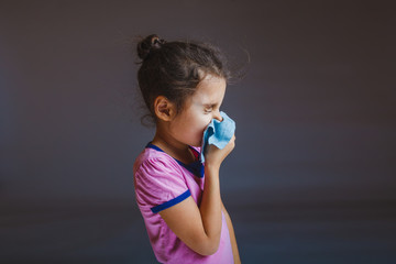 girl blowing his nose into handkerchief on a gray background
