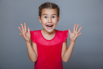 girl child holding hands at the mouth surprised on a gray backgr