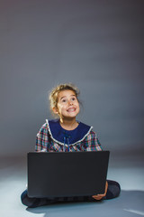 girl child sitting playing laptop surprised on a gray background