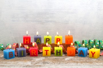 """Brennende """"Happy Birthday"""" - Kerzen auf Holzhintergrund"""