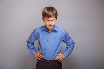 angry teenager boy on  gray background