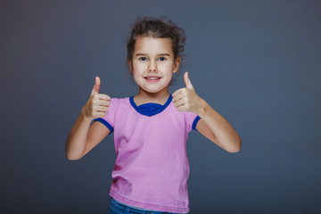little girl shows sign 'yes' fingers on gray background