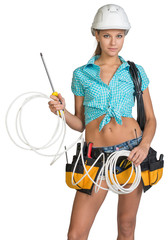 Pretty electrician in helmet, shorts, shirt, tool belt with