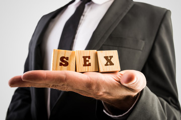 Businessman holding wooden alphabet blocks reading Sex