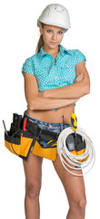 Serious electrician in helmet, shorts, shirt, tool belt with