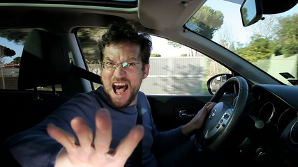 Man shouting into camera while driving pointing finger