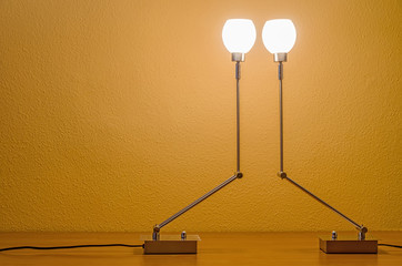 two lit modern lamps reaching up