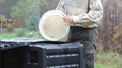 Compost. Man throws kitchen scraps into a composter