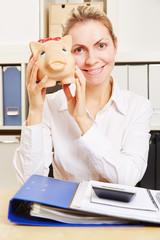Frau am Schreibtisch hält Sparschwein