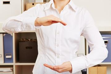 Frau im Büro hält Hände offen