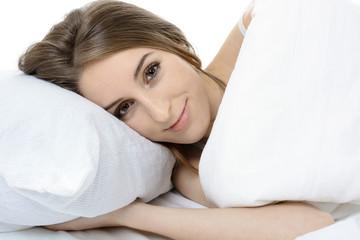 Frau in Bett beim Aufwachen nach Schlaf
