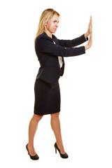 Geschäftsfrau schiebt ein imaginäres Objekt