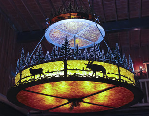 A Wrought Iron Chandelier Hangs in a Forest Lodge