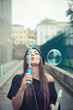 young beautiful brunette woman girl blowing bubbles soup