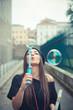 young beautiful brunette woman girl blowing bubbles soup