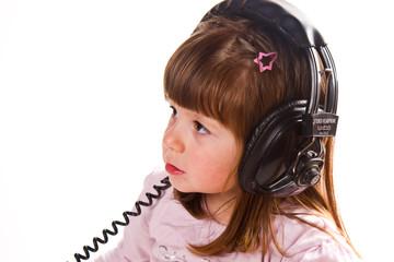 Beautiful cute happy little girl with headphones
