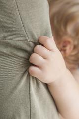 closeup baby hand holding mom dress