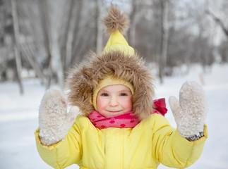 funny little girl in winter clothes in a snowy forest