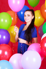 Portrait of a young attractive woman among many bright balloons