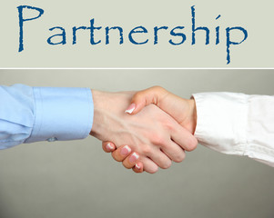 Business handshake symbolizing partnership on gray background