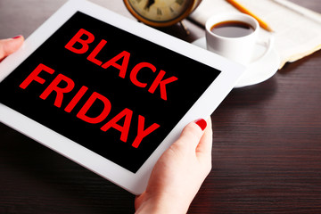 Hands holding tablet with Black Friday text