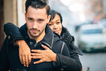 Young black woman hugging boyfriend on street