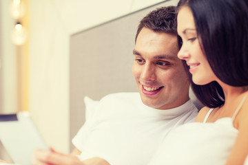 smiling couple in bed with tablet pc computers