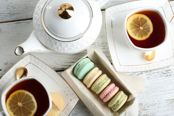 Colorful macaroons with teapot and cup of tea