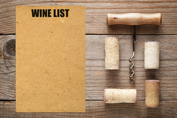 Wine list and corks with corkscrew on wooden background