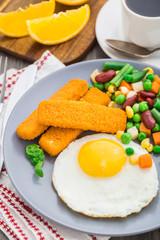 Fish sticks, fried egg and vegetables