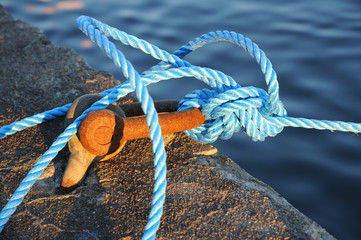 Rusty mooring with blue rope