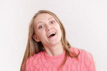 Portrait of the laughing girl on a light background