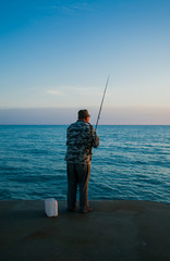 Old fisherman fishing in sea