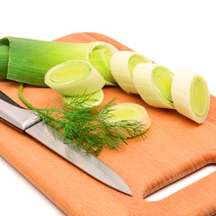 Fresh sliced leek and dill on a wooden board