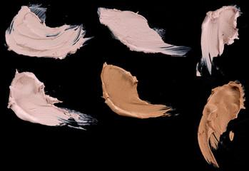 Various make up liquid powder strokes on black background