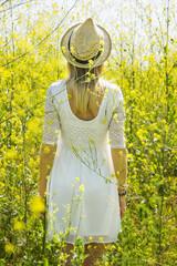 Girl in white dress in yellow field