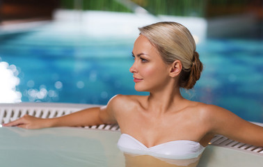 happy woman sitting in jacuzzi at poolside