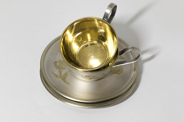 Two metallic saucer and coffee cup in stack