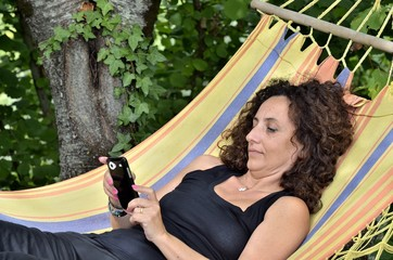 Mature woman relaxes on a hammock.