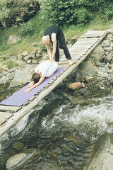 Woman and man doing yoga in nature